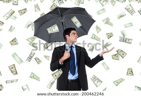 Stock image of businessman with umbrella and falling money - stock photo