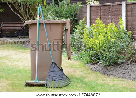 Stock image of garden waste in recycling container with lawn rake and sweeping brush in pleasant garden. - stock photo