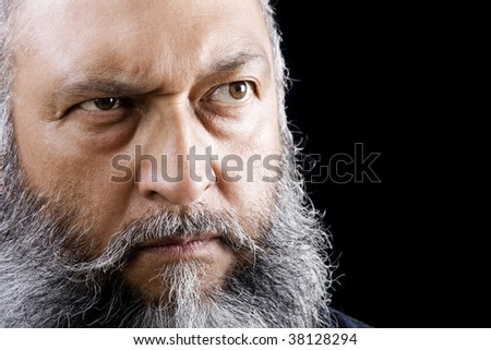 Stock image of menacing man with long beard over dark background