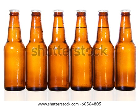 Stock image of six dark beer bottles over white background with reflection on bottom - stock photo