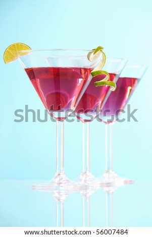 Stock image of three Cosmopolitan cocktails over blue background with reflection on bottom. Selective focus on front glass. Find more prepared drinks and cocktails in my portfolio. - stock photo