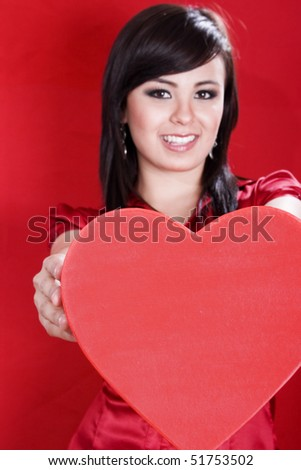 Stock image of woman holding heart shape over red background, selective focus on heart.