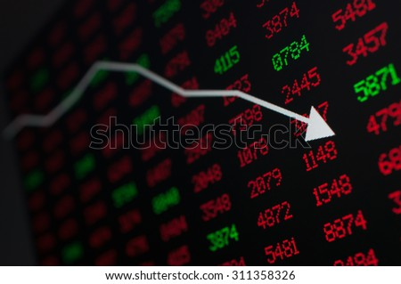 Stock Market - Arrow Graph Going Down on Display With Red and Green Figures - stock photo