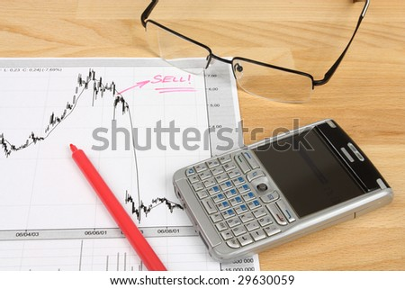 Stock market candle charts, smart phone, remarks with a red marker and glasses - stock photo