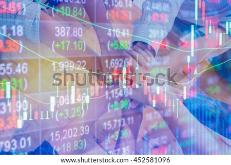 Stock market chart data on LED display concept.Group of people hands together on wooden background.