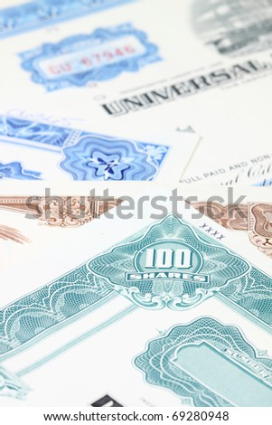 Stock market collectibles. Old stock share certificates from 1950s-1970s (United States). Vintage scripophily objects (obsolete) with shallow depth of field (focus on 100 shares). - stock photo