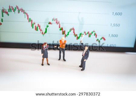 stock market graph, data analyzing with miniature people - stock photo