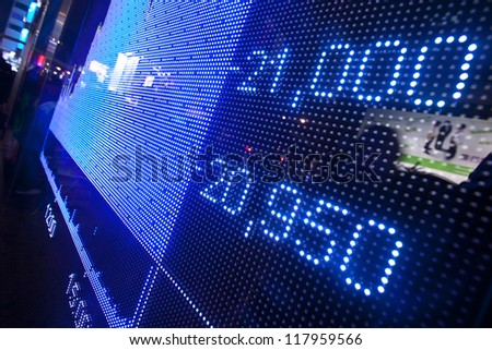 Stock market price display abstract in modern city - stock photo