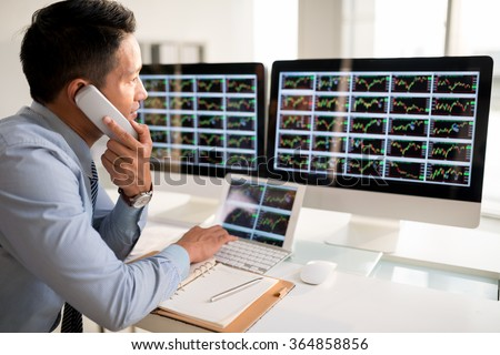 Stock market trader talking on telephone when looking at the monitor - stock photo