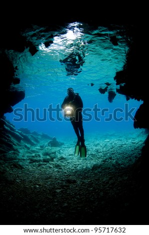 Stock Photo: Diver in front of an underwater cave - stock photo