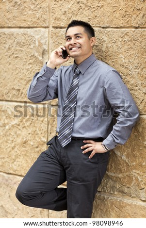 Stock photo of a Hispanic businessman leaning against a wall in a business district while chatting on a cell phone. - stock photo