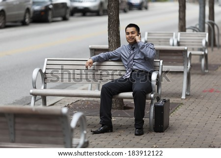 Stock photo of a Hispanic businessman sitting on a city bench and chatting on a cell phone with a happy expression. - stock photo