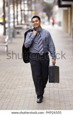Stock photo of a Hispanic businessman walking down the sidewalk in an urban business district carrying a coat over one shoulder and his breifcase.