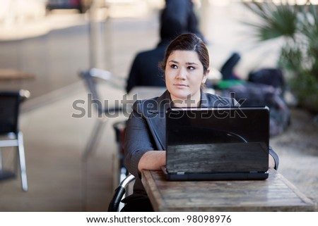 Stock photo of a well dressed businesswoman looking up from her laptop while telecommuting from an internet cafe.