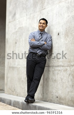 Stock photo of a well dressed Hispanic businessman leaning against a concrete wall and looking up. - stock photo