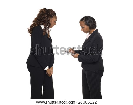 Stock photo of an African American businesswoman answering a questionaire being taken by another businesswoman.