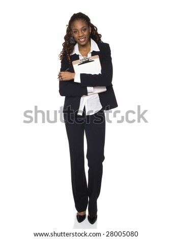 Stock photo of an African American businesswoman smiling at the camera while holding a clipboard to her chest. - stock photo