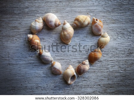 Stock photo of shells arranged in heart form on old gray background. Lens vignetting applied.  - stock photo