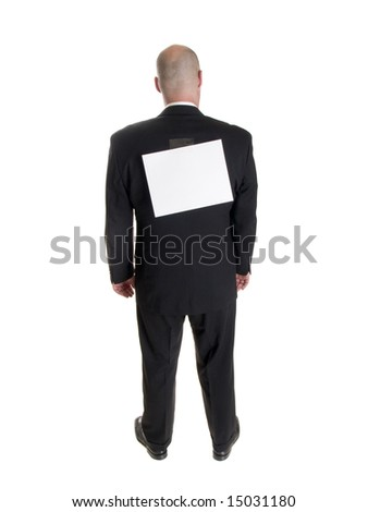 Stock photo of the back side of a well dressed businessman facing away from the camera with a blank sheet of paper taped to his back.