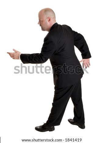 Stock photo of the side view of a well dressed businessman holding his hand out in a gesture as if pulling a rope or asking a woman to dance.  Full length, isolated white. - stock photo