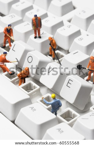 Stock photo of worker figurines posed around the word love spelled out with compute keys, on a keyboard. - stock photo