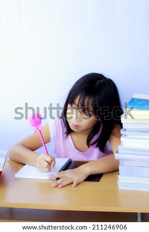 Stock Photo - Portrait of cheerful Asian young girl doing her homework