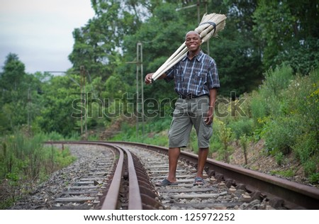 Stock photograph of a black South African entrepreneur small business broom salesman on railway line in Hilton, Pietermaritzburg, Kwazulu-Natal