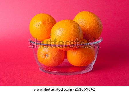 Stock picture of oranges in a glass bowl, on a red background - stock photo
