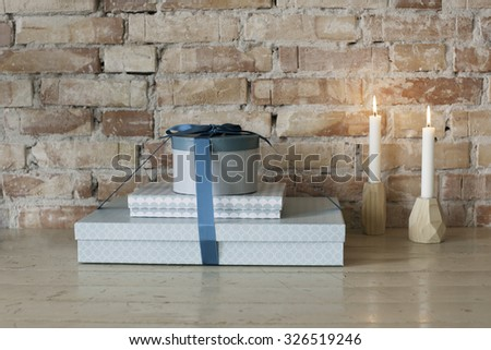 Stock picture of presents and candlelights on a wooden table, in front of a rough brick wall - stock photo