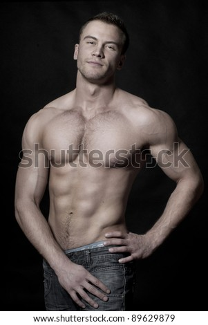 Stock portrait of sexy muscular young macho man on black background