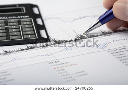 Stock price chart printout being analyzed. Pointing with a pen at chart features, with calculator ready. - stock photo