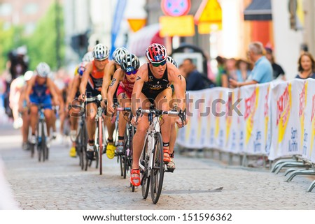 STOCKHOLM - AUG, 24: A group lead by Kate Mcilroy cycling on the crowded cobblestone road in the Womens ITU World Triathlon Series event Aug 24, 2013 in Stockholm, Sweden - stock photo