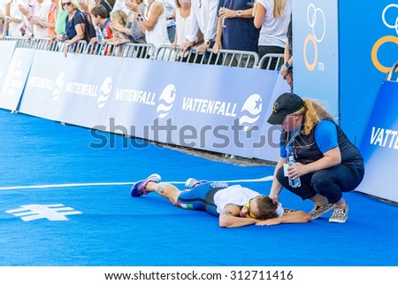 STOCKHOLM - AUG 22, 2015: Alice Betto (ITA) lies in the goal area and is very tired at the Womens ITU World Triathlon series event in Stockholm. - stock photo