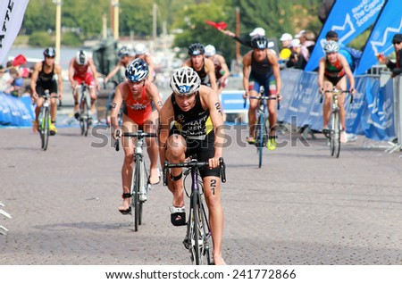 STOCKHOLM - AUG 23, 2014: Anja Knapp (GER) fixing the cycling shoe after the swimming in the transition zone in the Women's ITU World Triathlon series event August 23, 2014 in Stockholm, Sweden - stock photo