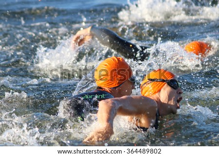 STOCKHOLM - AUG 23, 2015: Close-up of swimming chaos of male swimmers wearing orange swimming caps at ITU World Triathlon event in Stockholm, 2015 - stock photo