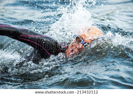 STOCKHOLM - AUG, 23: Closeup of a triathlete swimming in the cold water at the Womans ITU World Triathlon Series event August 23, 2014 in Stockholm, Sweden - stock photo