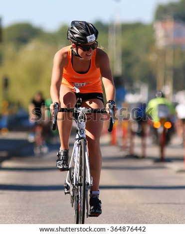 STOCKHOLM - AUG 23, 2015: Cycling young woman wearing oranges tank top and sun-glasses at ITU World Triathlon event in Stockholm, 2015 - stock photo