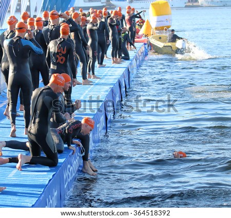 STOCKHOLM - AUG 23, 2015: Large group of male triathletes wearing black swimsuit and orange swimming cups waiting for the start at ITU World Triathlon event in Stockholm, 2015 - stock photo