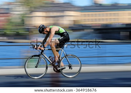 STOCKHOLM - AUG 23, 2015: Rapid cycling man on black racing bike, the speed makes it un-sharp at ITU World Triathlon event in Stockholm, 2015 - stock photo