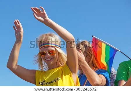STOCKHOLM - AUG - 01. Stockholm Pride parade crossing the street with the name Skeppsbron 1 August 2015. Dancing girl dressed in yellow shirt and sunglasses.