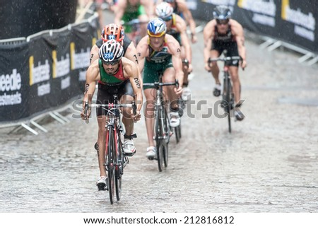 STOCKHOLM - AUG, 23: Triathletes in heavy rain with Joao Silva in front on the wet cobblestone at the Mens ITU World Triathlon Series event August 23, 2014 in Stockholm, Sweden
