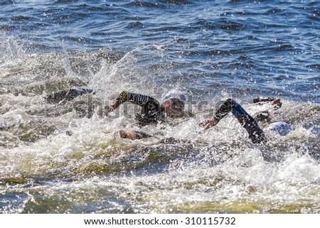 STOCKHOLM - AUG 22, 2015: Triathlon start in chaos with water splashes at the Womens ITU World Triathlon series event in Stockholm. - stock photo