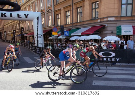 STOCKHOLM - AUG 22: Women ITU World Triathlon event Aug 22 2015. Woman cycling in Old town.