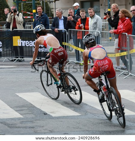 STOCKHOLM - AUG 23, 2014: Zsofia Kovacs and Ainhoa Murua cycling in a curve in the Women's ITU World Triathlon series event August 23, 2014 in Stockholm, Sweden - stock photo
