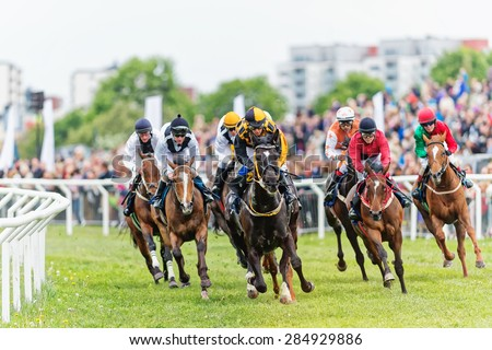 STOCKHOLM - JUNE 6: Action when jockeys and horses coming out from the last curve at the Nationaldags Galoppen at Gardet. June 6, 2015 in Stockholm, Sweden. - stock photo