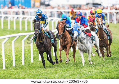 STOCKHOLM - JUNE 6: Group of jockeys out of the fourth curve at the Nationaldags Galoppen in Gardet. June 6, 2014 in Stockholm, Sweden. - stock photo