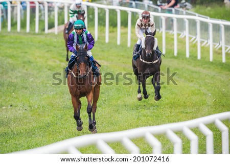 STOCKHOLM - JUNE 6: Jockeys into a curve at the Nationaldags Galoppen in Gardet at a warm up lap. June 6, 2014 in Stockholm, Sweden. - stock photo
