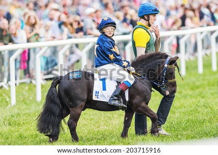 STOCKHOLM - JUNE 6: Pony racer warming up with her trainer and horse before the start of childrens race at Nationaldags Galoppen. June 6, 2014 in Stockholm, Sweden. - stock photo