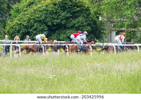 STOCKHOLM - JUNE 6: Riders passing the far side at the Nationaldags Galoppen in Gardet. June 6, 2014 in Stockholm, Sweden. - stock photo