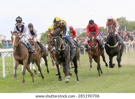 STOCKHOLM - JUNE 06: Tough race between the race horses coming out of the first curve at the Nationaldags Galoppen at Gardet. June 6, 2015 in Stockholm - stock photo